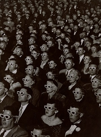 Audience watches movie wearing 3-D spectacles,1952